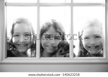 three sister friends looking through the window with a pup and raindrops - stock photo
