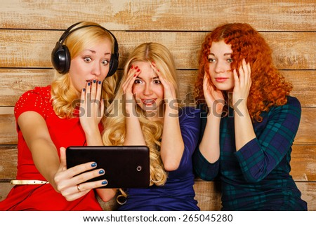 Three sisters, blond and red, listening to music on headphones. Girls are very surprised, looking at screen the tablet PC, making fun selfie. Sisters sitting in the bedroom. - stock photo