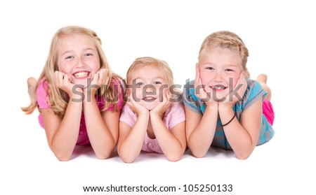 Three sisters laying on white background smiling