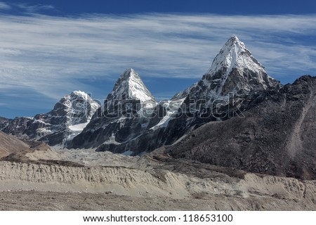 Three sisters Nirekha (6169 m), Kangchung (6062 m), and Chola (6069 m) in the area of Cho Oyu - Gokyo region, Nepal - stock photo