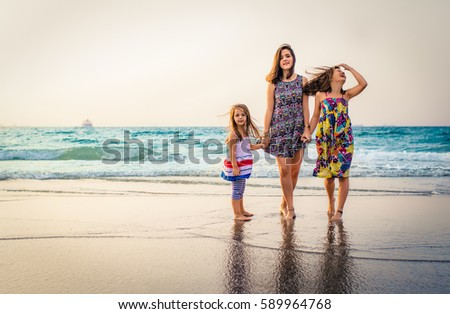 three sisters standing at the beach