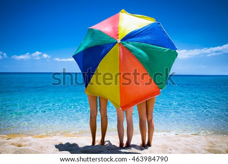 Three sisters under the umbrella on the beautiful beach in Greece