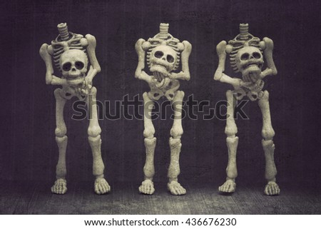 Three skeletons holding their own head with black background grungy textured - stock photo