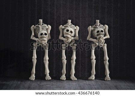 Three skeletons holding their own heads - stock photo