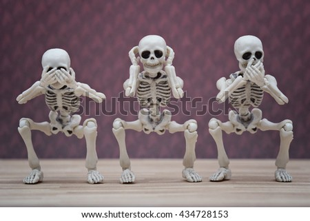 Three skeletons poses hear no evil, see no evil, speak no evil