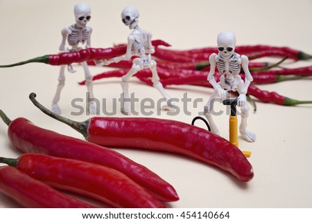 Three skeletons pumping red chili pepper  - stock photo