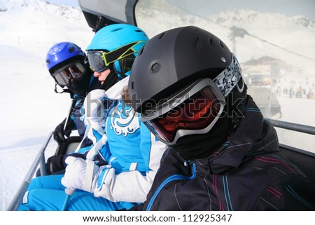 Three skiers in helmets and goggles ride on funicular in mountains. Focus on boy.