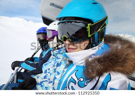 Three skiers in special clothing and helmets ride on cable car in mountains. - stock photo