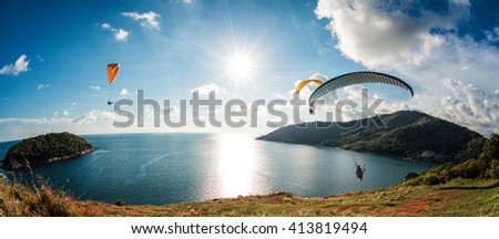 Three Skydiver flying over the water during sunset with the mountains - stock photo