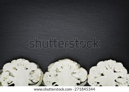 Three sliced white cauliflowers isolated on a dark grey stone slab with empty copy space. - stock photo