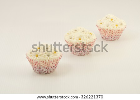 Three small cupcakes in heart design prints paper cup arranged in row on white background.  The cake have beautiful decorative fondant topping of white floral with golden and silver edible beads.   - stock photo