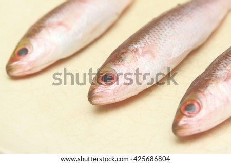 three small fresh fish close up to head prepared for cook lay down on dish or plate - stock photo