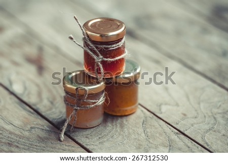 Three small jars of marmalade or jam on wooden table. Toned image - stock photo