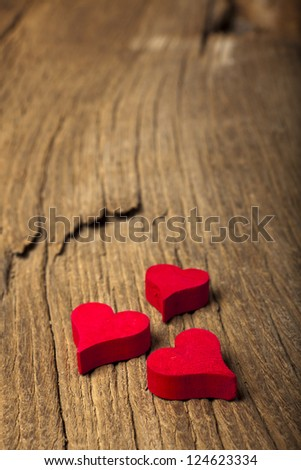 Three small red wooden hearts on a old wooden board - stock photo