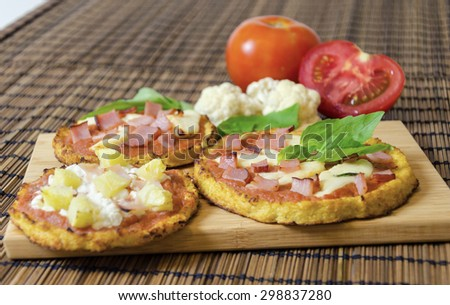 Three small round baked pizzas made of cauliflower crust and topped with bacon,ham,halloumi cheese,cottage,lountza,pineapple,turkey,tomato sauce,basil on a wooden chopping board. A healthy pizza snack - stock photo