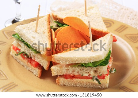 three  small sandwiches with potato crisps - stock photo