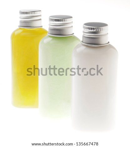 Three small transparent plastic bottles filled with green, pastel green and white cosmetic lotions/creams and sealed with silver metal caps. The contents of the bottle can be lotion, shampoo, etc. - stock photo
