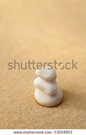 three small white stones on a sand, vertical photo, shallow depth of view