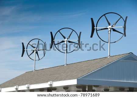 Three smaller wind turbines located on top of a gasoline station - stock photo