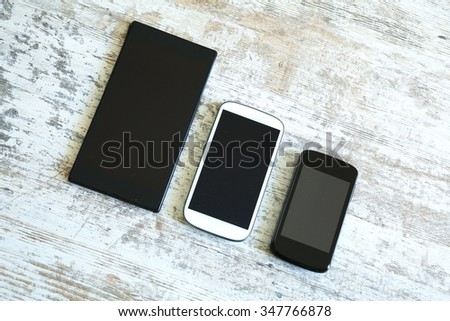 Three smartphone in different sizes on a wooden table. - stock photo