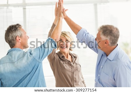 Three smiling business colleagues giving high-five at the office