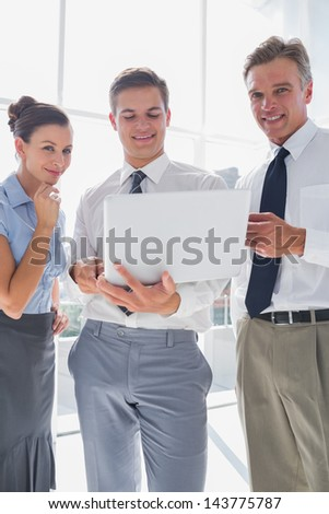Three smiling business people using a laptop in a modern office