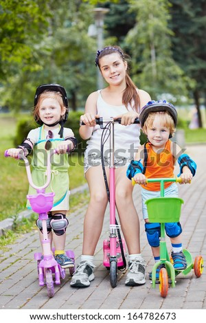 Three smiling children scooterists in summer park
