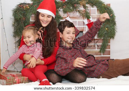 Three smiling children sitting near Christmas decorated fireplace, winter holiday family concept - stock photo