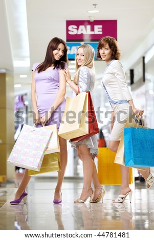 Three smiling elegant girlfriends to the utmost on shopping - stock photo