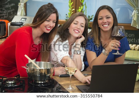 Three smiling girlfriends having fun in the kitchen. They are using computer and searching for a recipe online while preparing food and drinking wine.