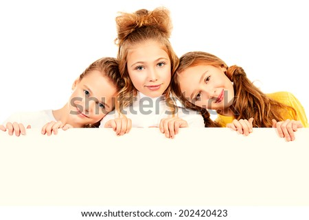 Three smiling girls standing together and hold white board. Isolated over white.