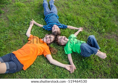 Three smiling happy kids lying down together on green grass meadow
