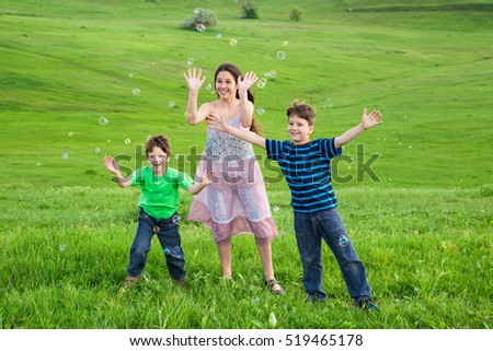 Three smiling kids catch the soap bubbles on green lawn