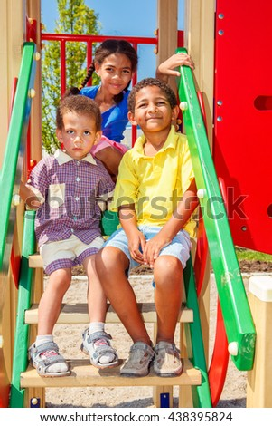 Three smiling kids enjoying summer at the outdoor playground