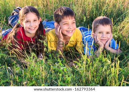 Three smiling kids lying on the green grass meadow - stock photo