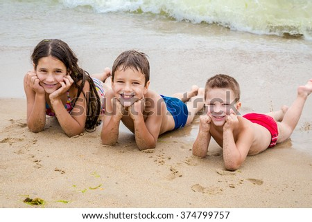 Three smiling kids on the beach lying down on the sand near water