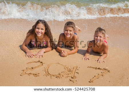 Three smiling kids on the beach lying down on the sand near water with new year 2017 sign