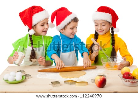 Three smiling kids with Christmas cooking, isolated on white