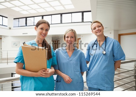 Three smiling nurses in stairwell