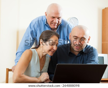 Three smiling people sitting at work on  laptop - stock photo