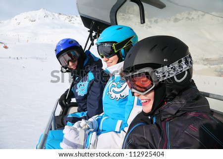 Three smiling skiers in helmets and goggles ride on funicular in mountains. Focus on boy. - stock photo
