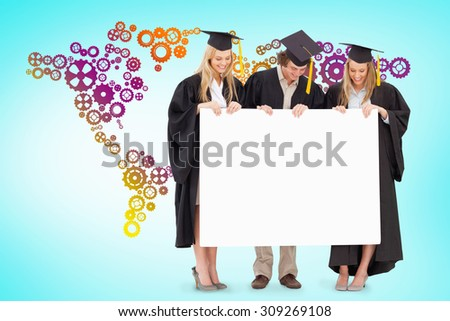 Three smiling students in graduate robe holding a blank sign against blue vignette background - stock photo