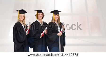 Three smiling students in graduate robe holding a diploma against bright white room with windows - stock photo