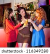Three smiling women in a bar holding glasses making a toast. - stock photo