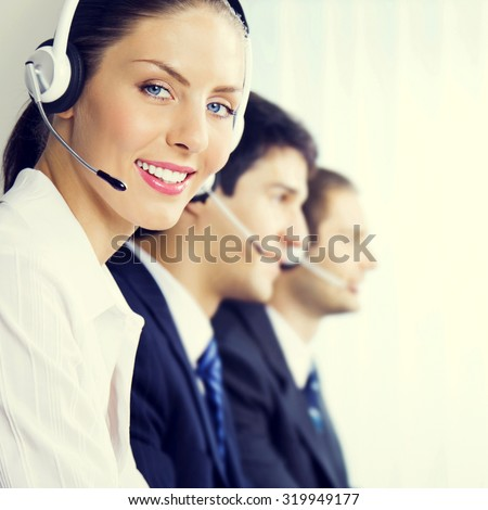 Three smiling young customer support phone operators at workplace, customer service concept
