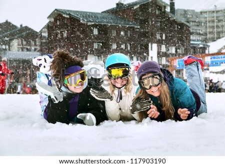 Three smiling young girls are snowboarders on the snow in mountains in French Alps the background of falling snow - stock photo