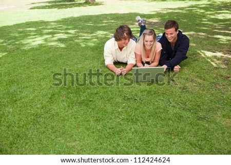 Three smiling young people in a park lying while using a laptop - stock photo