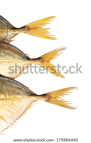 Three smoked fish tails isolated on white - stock photo