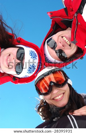 Three snowboarders standing in huddle, smiling, low ange view. - stock photo