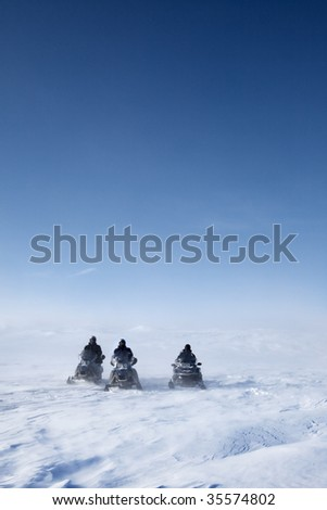 Three snowmobiles on a winter landscape with blowing snow